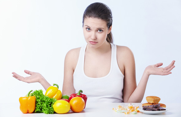 woman-with-fruit-and-junk-food-on-the-table